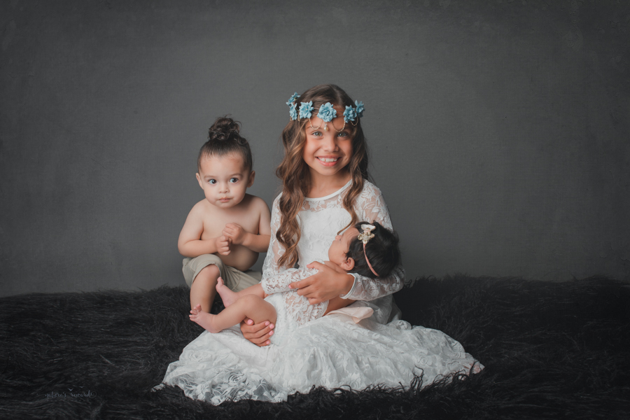 Newborn baby girl and her big brother and big sister in newborn portrait by Nature's Reward Photography.