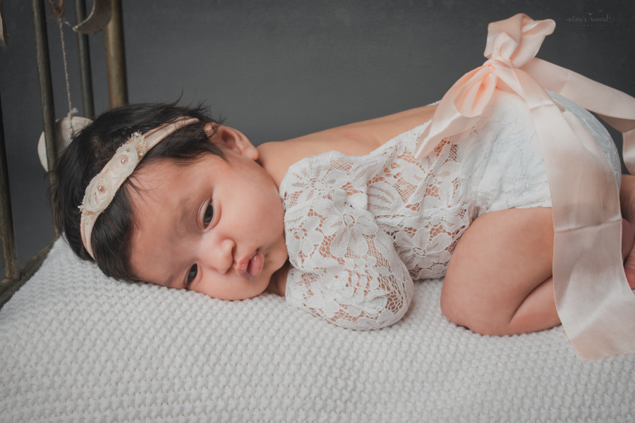 Newborn baby girl on a doll bed surrounded by flowers in this newborn portrait by Nature's Reward Photography