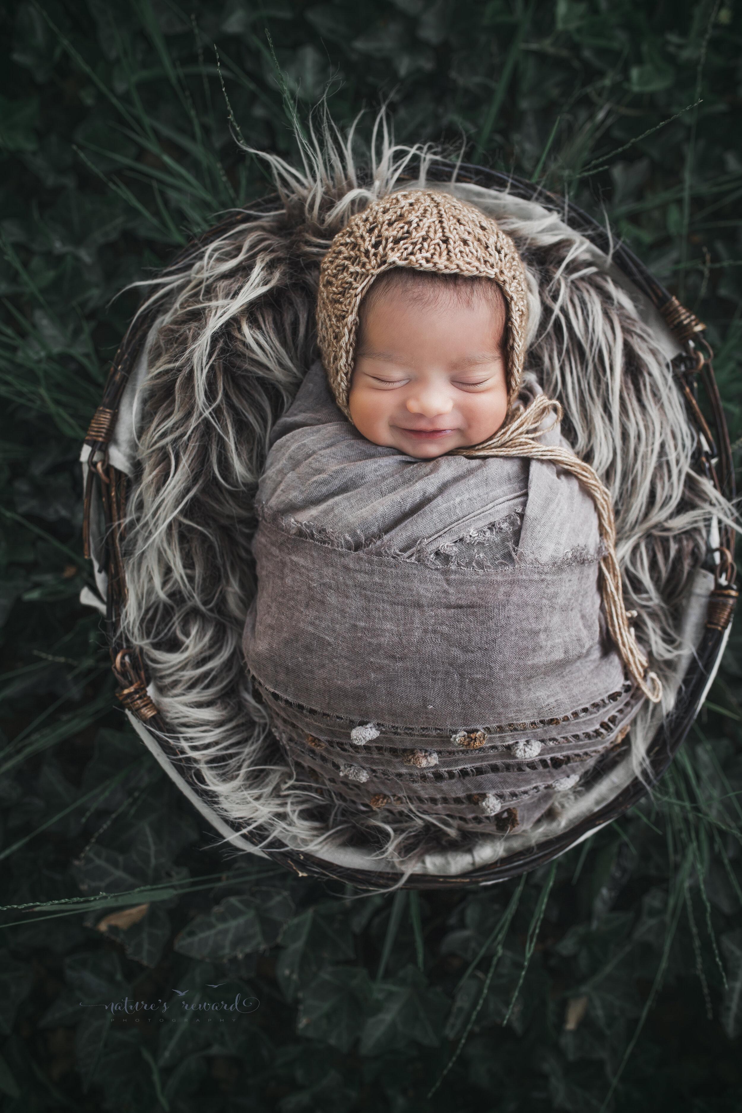 Newborn baby Girl in the garden smiling, a newborn portrait by Nature's Reward Photography