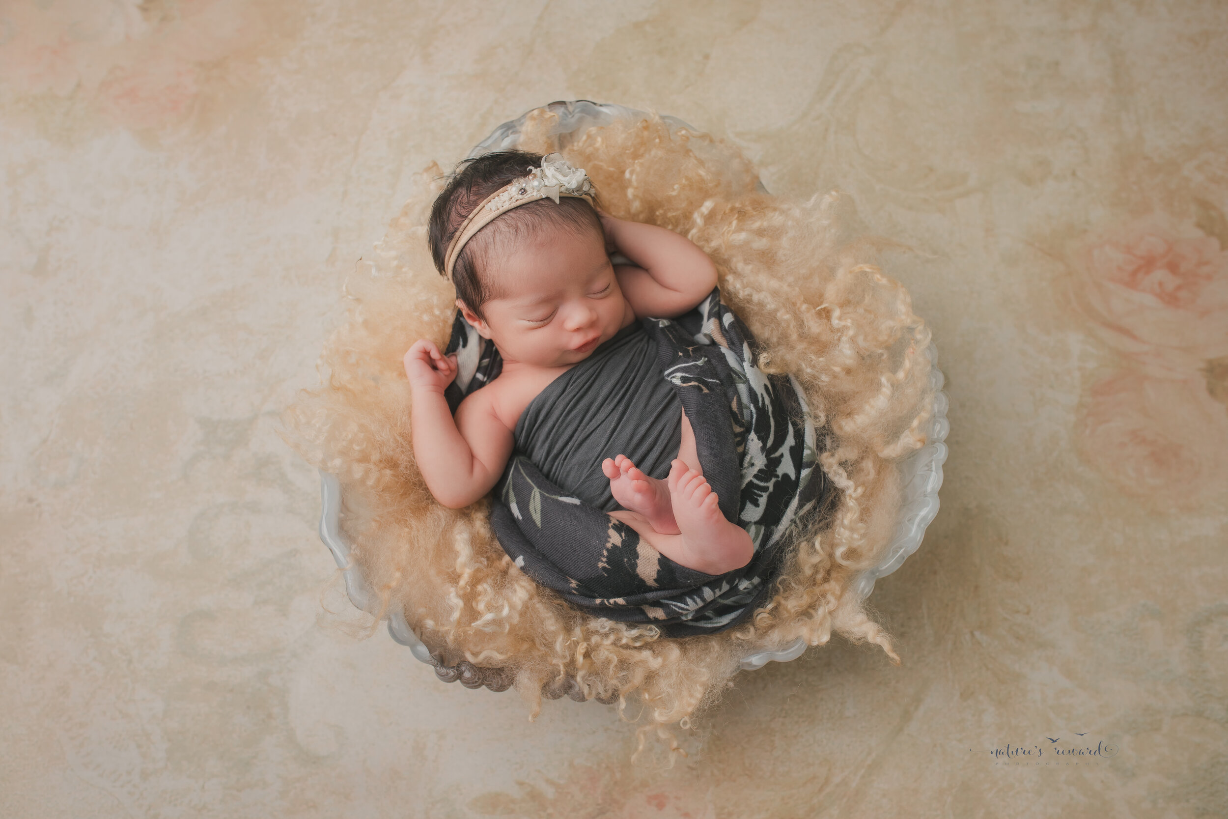 Newborn Baby girl stretching while swaddled in grey in an ivory bowl on a floral backdrop,a newborn portrait by Nature's Reward Photography