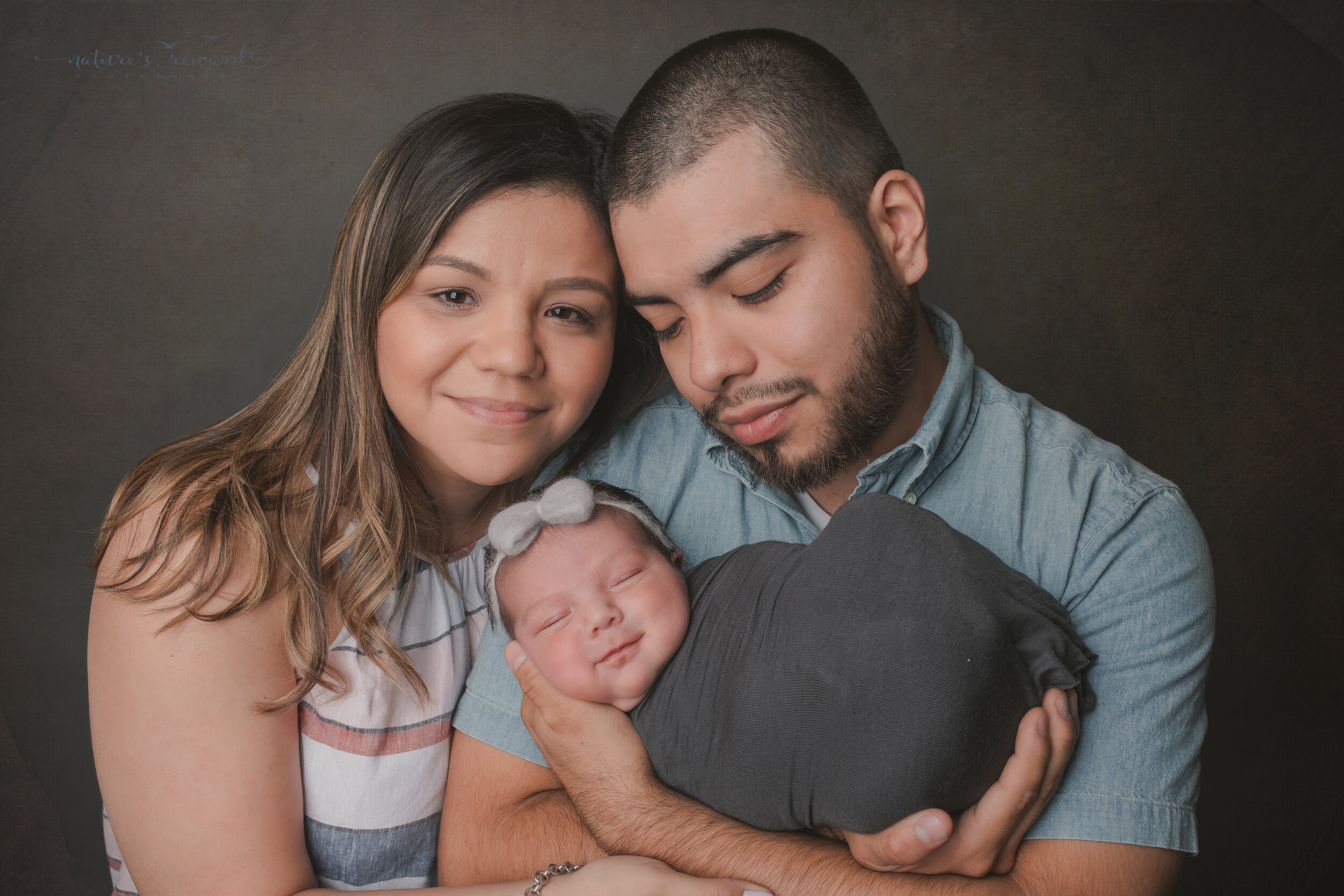A newborn baby girl and her family in this portrait by Nature's Reward Photography