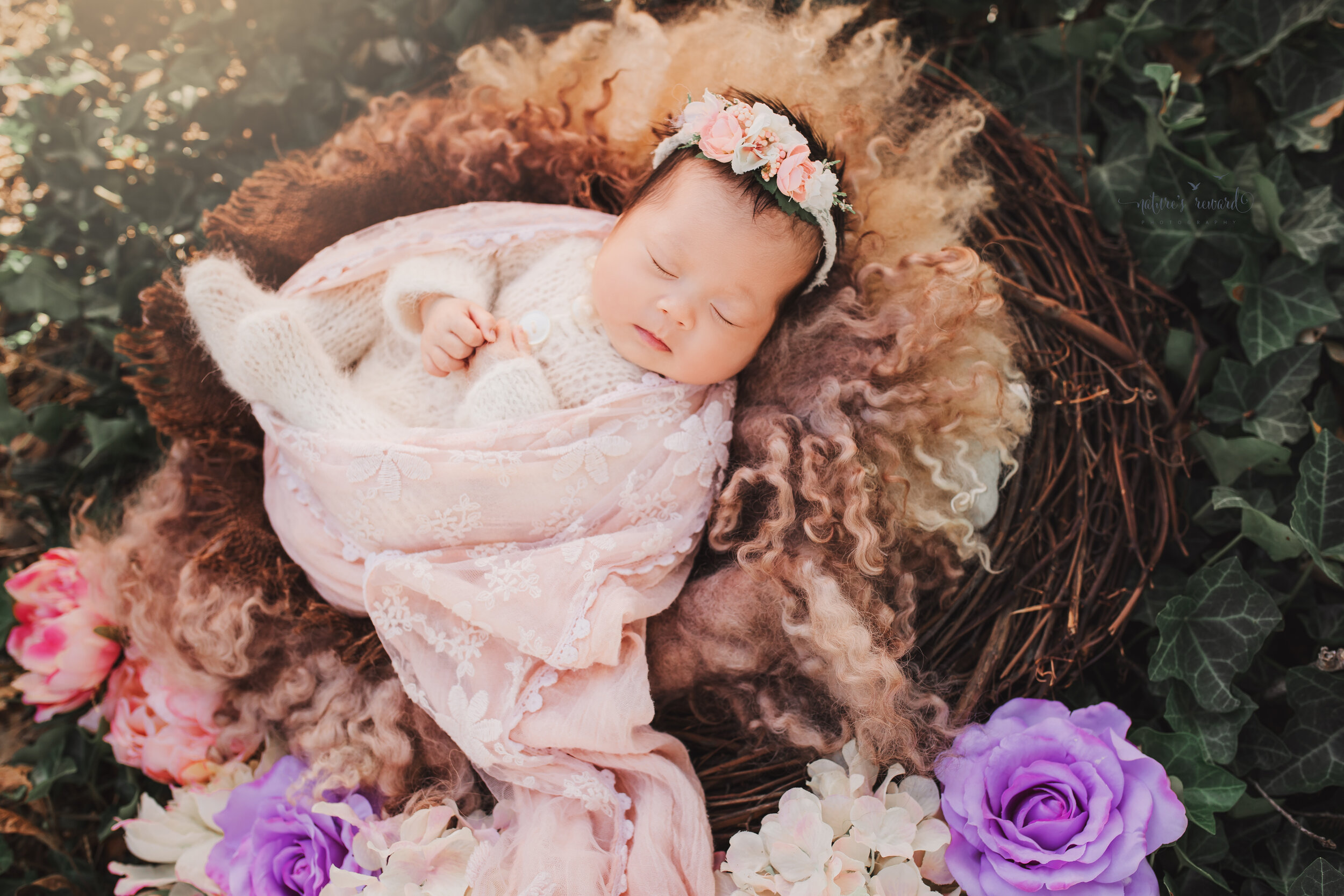 Newborn Baby girl in a pink swaddle in a nest in a garden portrait by nature's Reward Photography