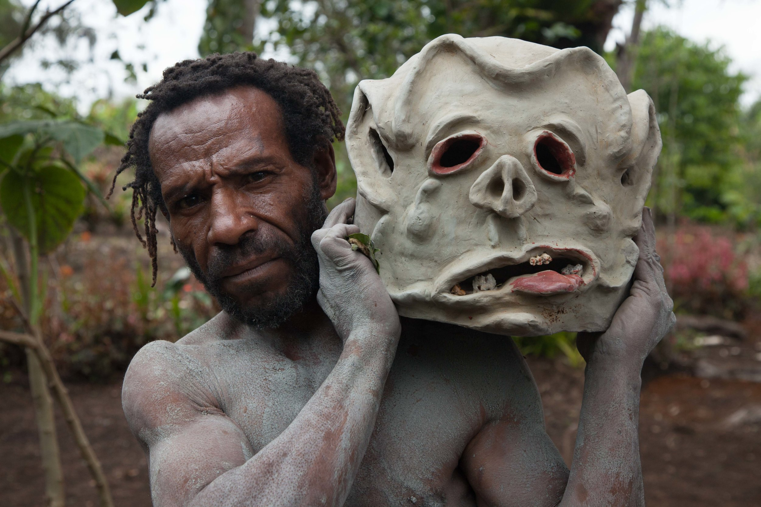 One of the famous  Asaro Mudmen  shows off his clay mask. Eastern Highland province
