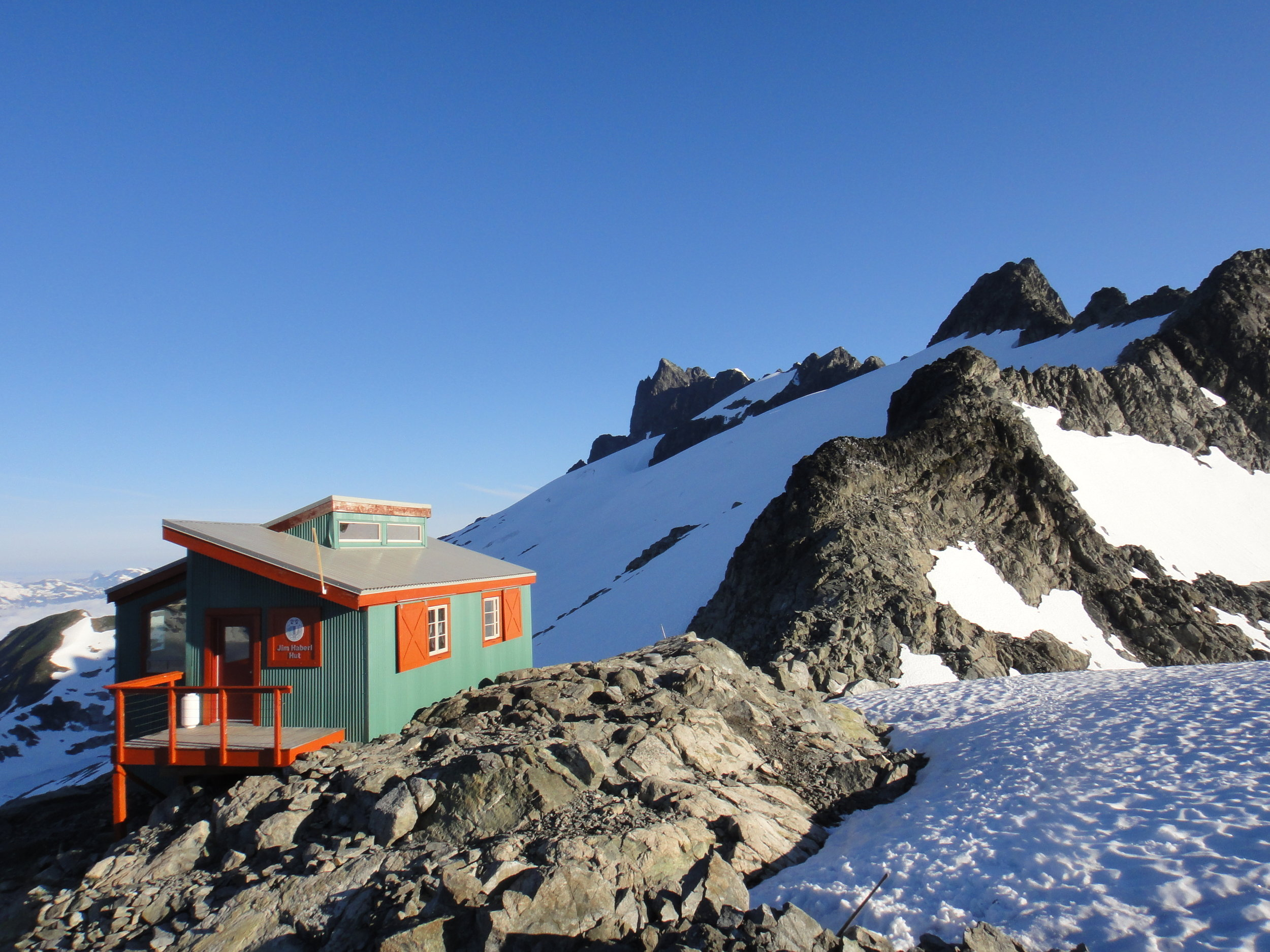 Jim Haberl Hut (Serratus Col):   For the higher, more remote Tantalus ridge area, from the Jim Haberl Hut at 6,700ft, to the Zenith col, Mt Dione, the Alpha ridge and Mt Ossa, allowing you and your group to access new heights for Alpine climbing and skiing in both summer and winter.   Cost:  $600 one way, $1200 round trip - for up to 5 passengers    Click Here   to reserve the cabin.