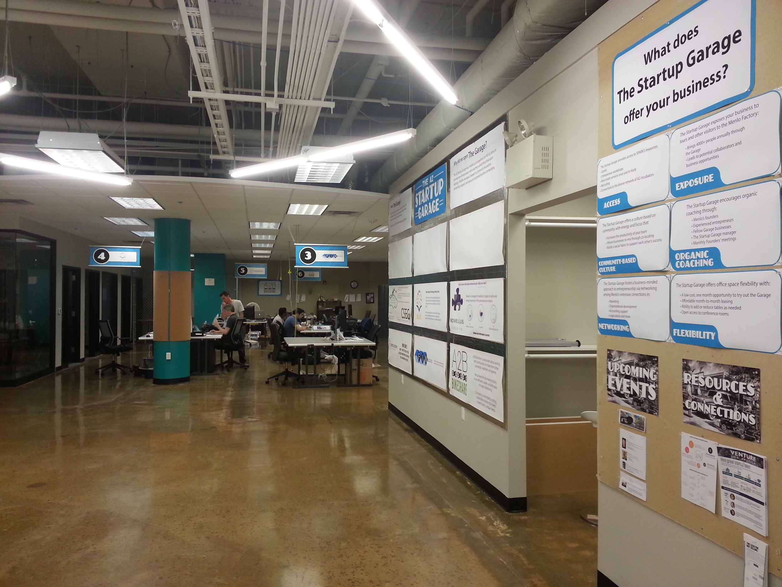 A promotional wall, visible from Menlo Innovations' large classroom space, features a panel for each startup with their logo and central focus