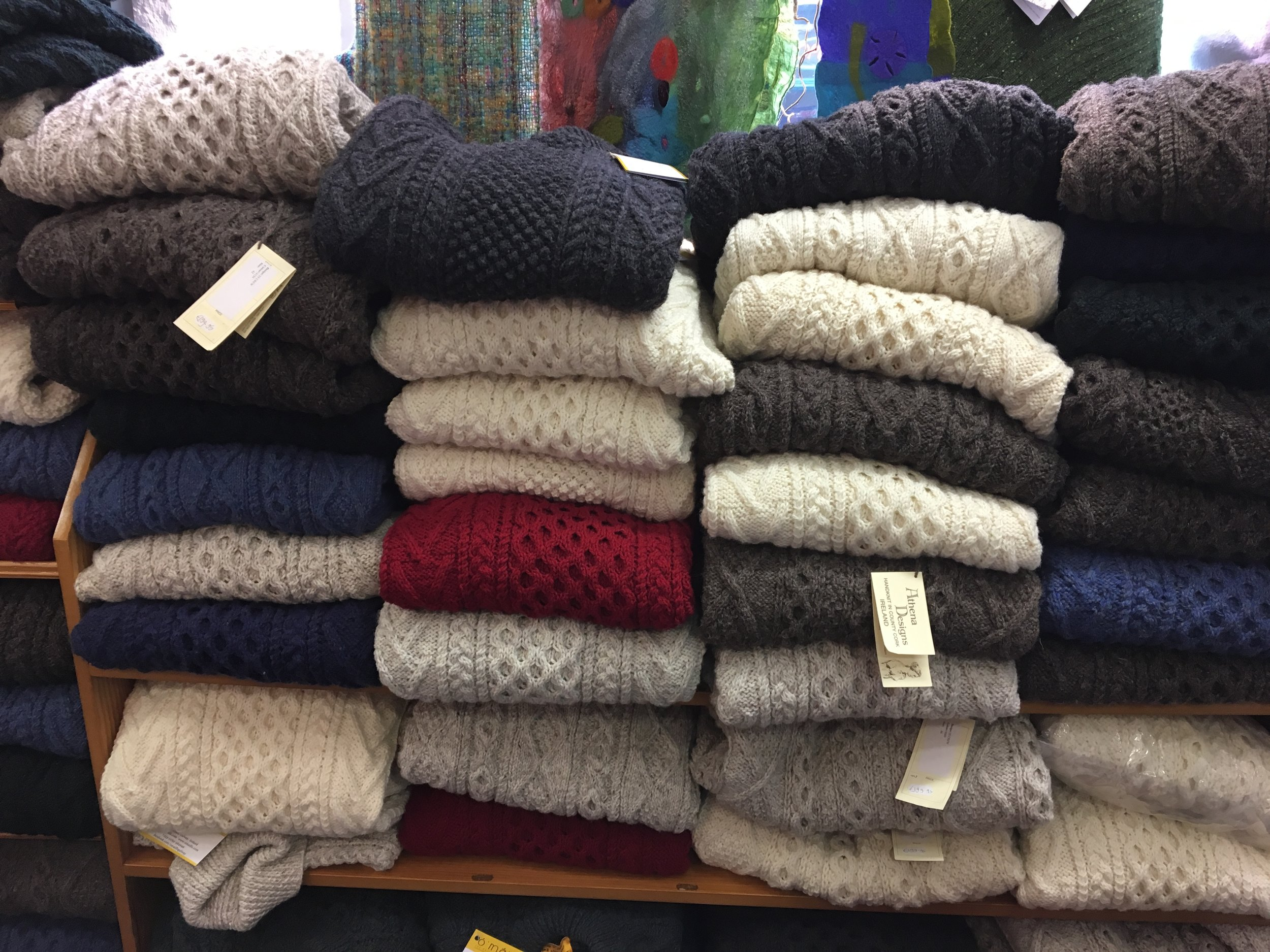 Stacks and stacks of handknit sweaters.