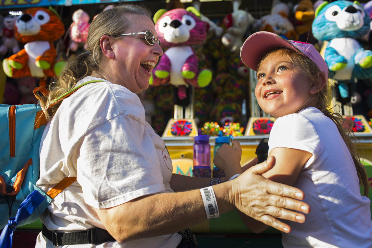 """Renee Nuzzo, left, of Mexico, reacts to daughter Kassondra Nuzzo, 7, winning a water race game on Saturday, Aug. 27, 2016 during the New York State Fair in Syracuse, N.Y. """"My arms aren't big enough,"""" she said after turning down the opportunity to play again."""