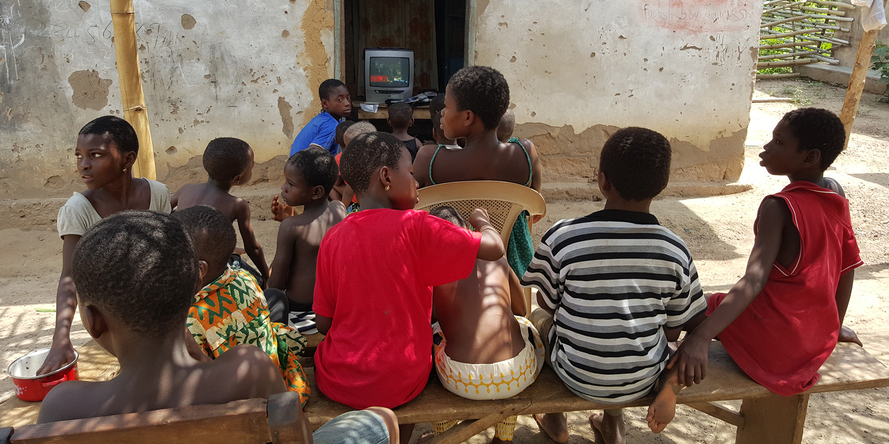 Young people gather to watch a TV show from an old box television set in rural Africa.