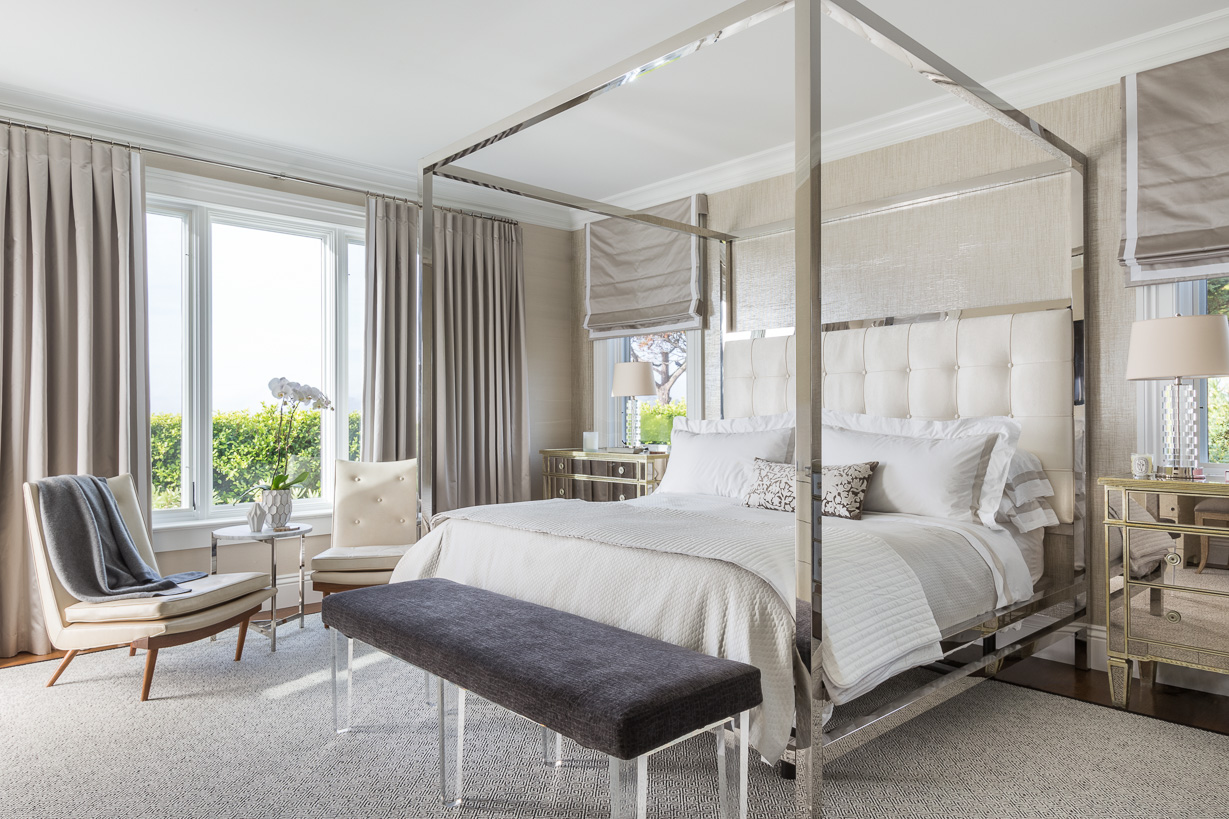 Unabashed glamour wins out in the master suite, which features a mirrored four-poster from Bernhardt and side tables by Horchow. At the foot of the bed, a Wisteria bench upholstered in a Colefax & Fowler fabric boasts contemporary Lucite legs.