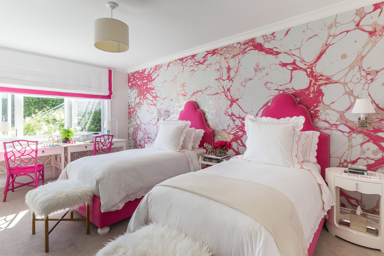 Lowengart embraced bold color in one of the daughters' rooms with a marble motif wallpaper by Calico, hot pink headboards, and desk chairs by Society Social. The bedside tables and desks are all by Serena & Lily.