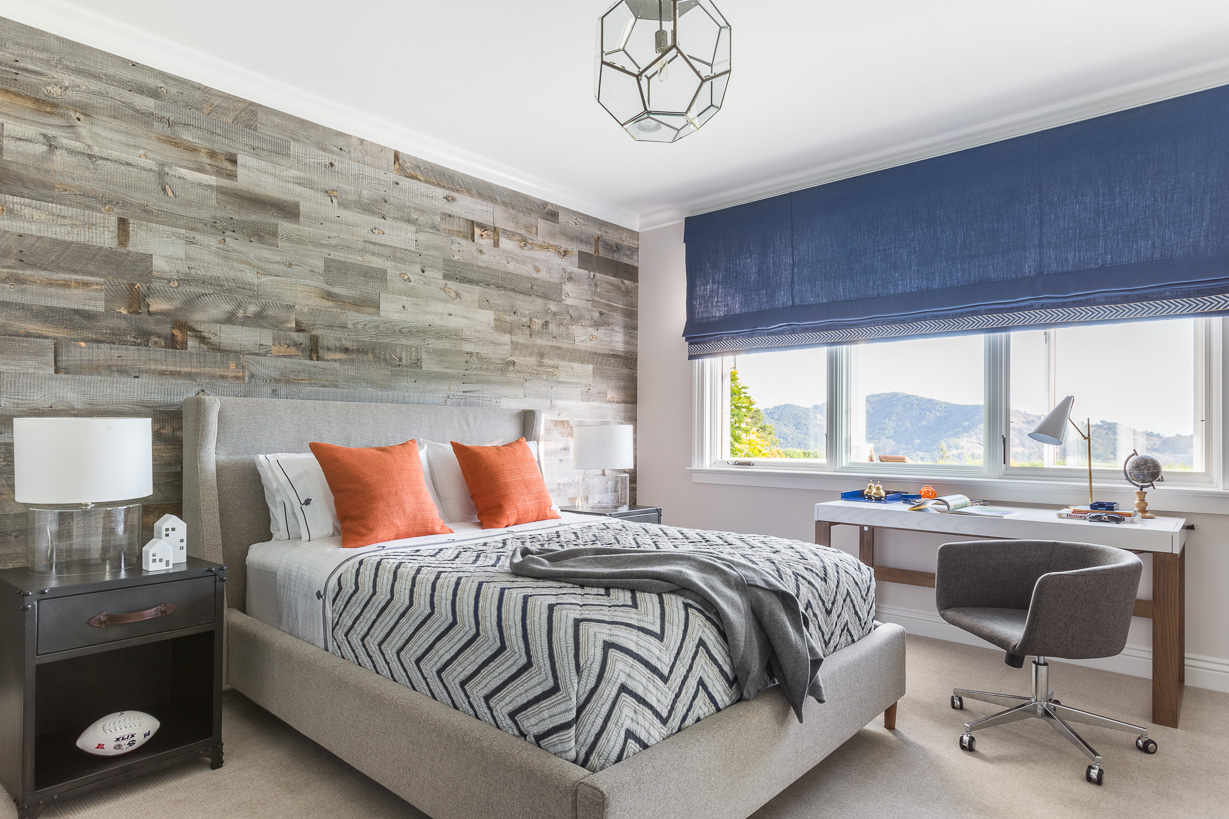 In the ten-year-old son's room, the headboard wall features a faux-bois covering by Stikwood. The ceiling pendant and bedside tables are by RH.