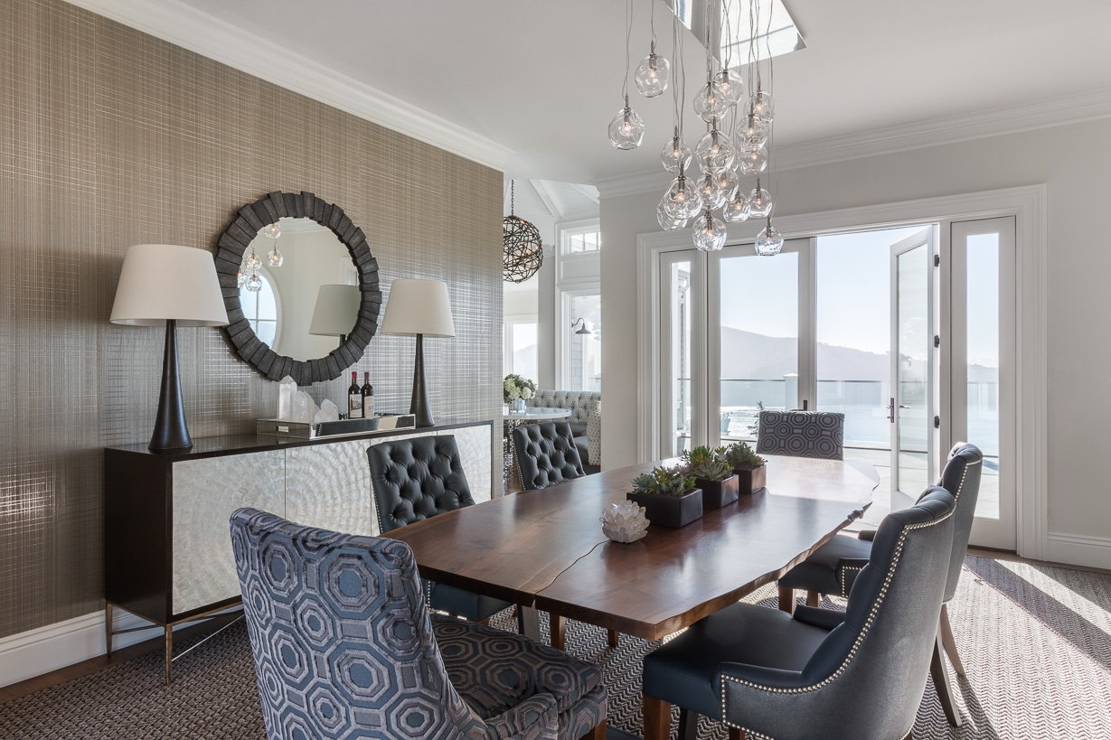 A wall covering by Phillip Jeffries and ceiling fixture by John Pomp lend the dining room a laid-back, coastal feel. The host chairs are covered in a Christopher Hyland print that echoes the octagonal pattern of the living room rug.