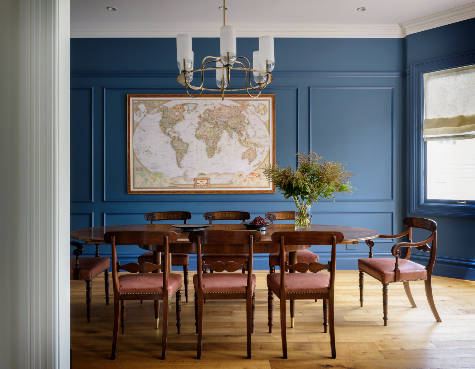 JKA Design  selected a rich blue wall color for the dining room of this Cole Valley Victorian. It is the perfect backdrop for the clients' collection of antique maps.