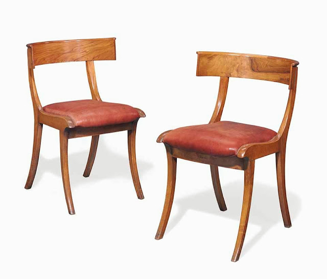 A Pair Of Danish Walnut Klismos Chairs First Half 19th Century with later close-nailed red leather upholstery from the estate of Anthony Hail, image from Christie's