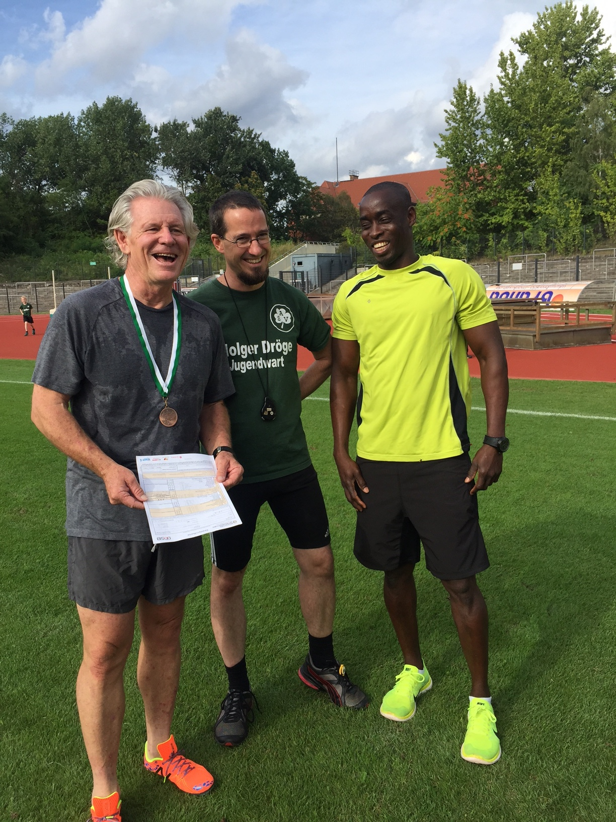 Here  Club Trainers Droege and David give me grief about the slow 100m and 200m times that were recorded forever in the ASV Berlin Athletics Club official register. Oh, and the medal was awarded to me by the club.
