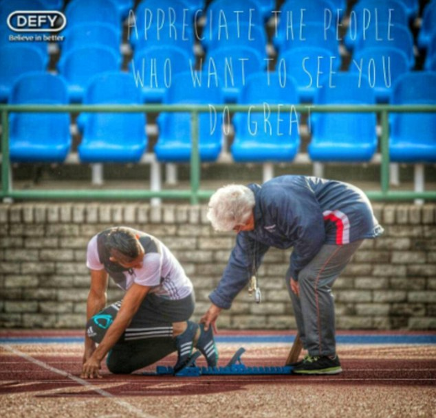 Ans Botha, Wade van Niekerk's 74-year-old coach, helps him with the starting blocks.