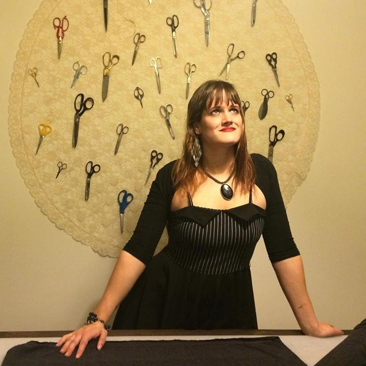 Artist and woman business owner, Skye Blue, poses with tailoring scissors in background