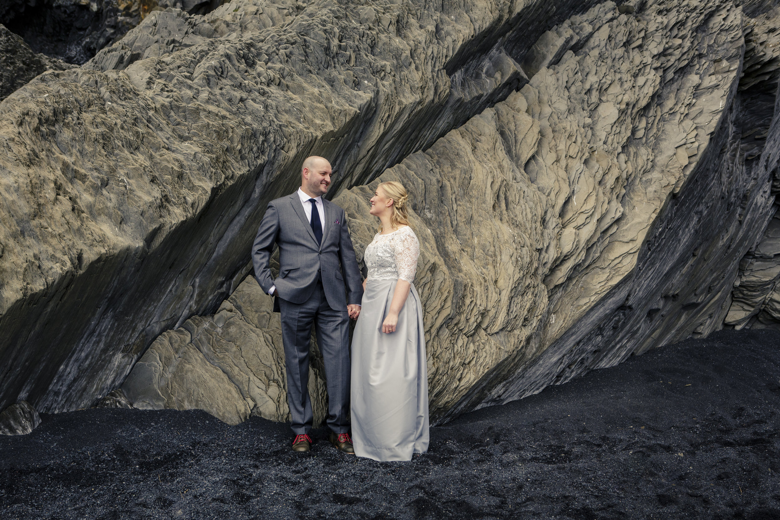 Bride and groom in front of rock feature in Iceland; bride wears dress with carefully crafted pleat at the waist and lace sleeves.