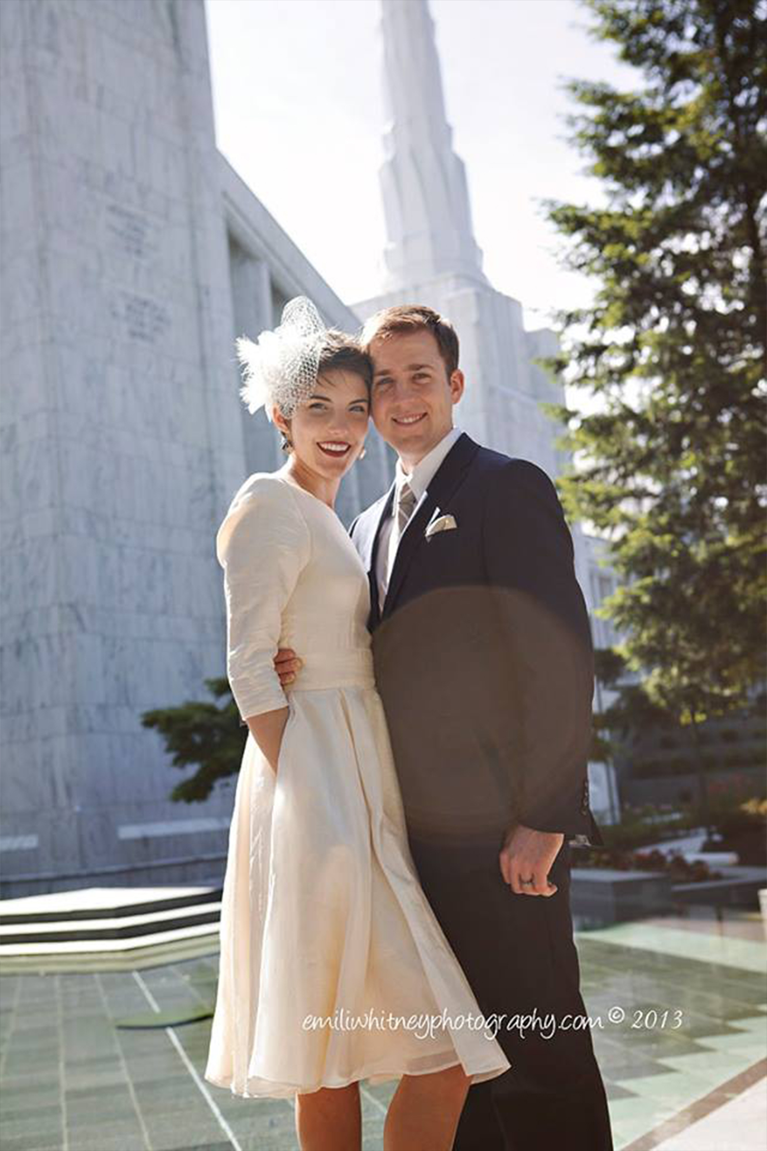 Bride and groom pose in front of temple. Bride wears modest wedding gown in silk and lace fascinator.