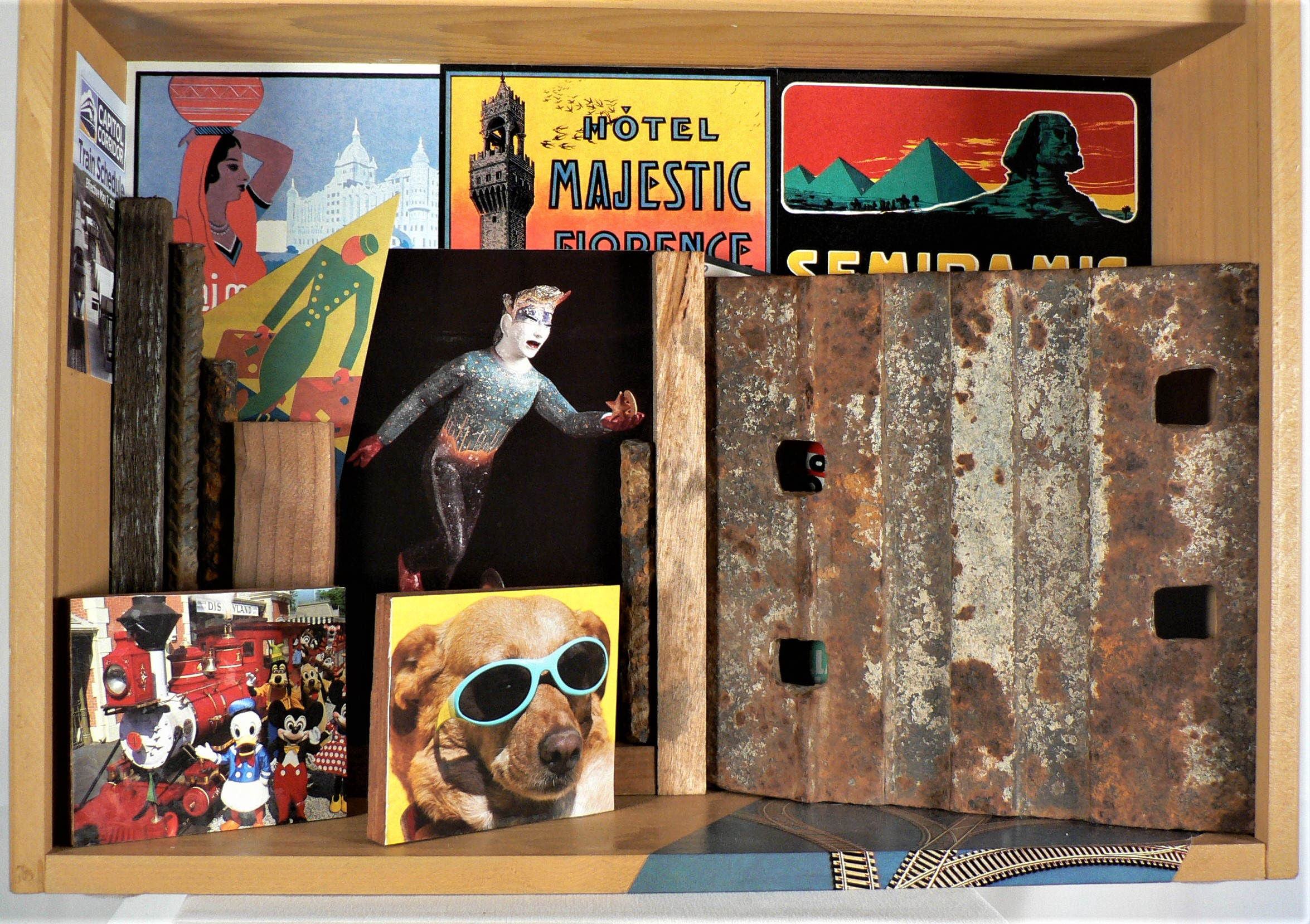 """Lost Track - """"Half the fun of travel is the esthetic of lostness."""" – Paul TherouxMaterials: California rice wood box; metal trolley segment; paper luggage label reproductions (Saturn Press); paper Conoco ad image; art postcard of Yoshio Taylor ceramic statute (Natsoulas Gallery); Disneyland postcard; Wag Hotel postcard; rebar; paper; acrylic paint. Dimensions: 13""""H x 17.5""""W x 5""""D. Created: December 2018.Status: For Sale ($300)"""