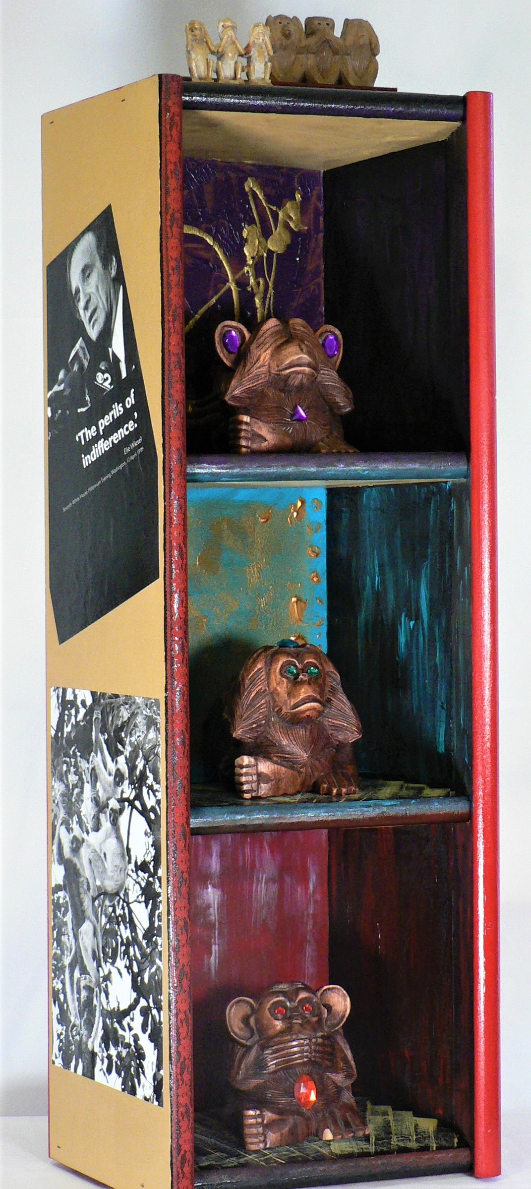 "Indifference - ""The Perils of Indifference."" – Elie Wiesel.Materials: Wood monkey carvings (source unknown); stone monkey carving (my father's desk); postcard image Japan c 1930 (Ulrich Collection); African monkey image (Genesis, Lisa Salgado & Sebastiao Salgado); Wiesel image from Speeches that Changed the World; Michelangelo's Fall of Man image (Sistine Chapel, Vatican); Bhairav (Hindu diety of destruction) image (Himalayan Spirit calendar, Craig Lovell, 2005); lace; acrylic paint; wood. Dimensions: 30""H x 11""W x 9.5""D. Created: February 2019.Status: For Sale ($250)"