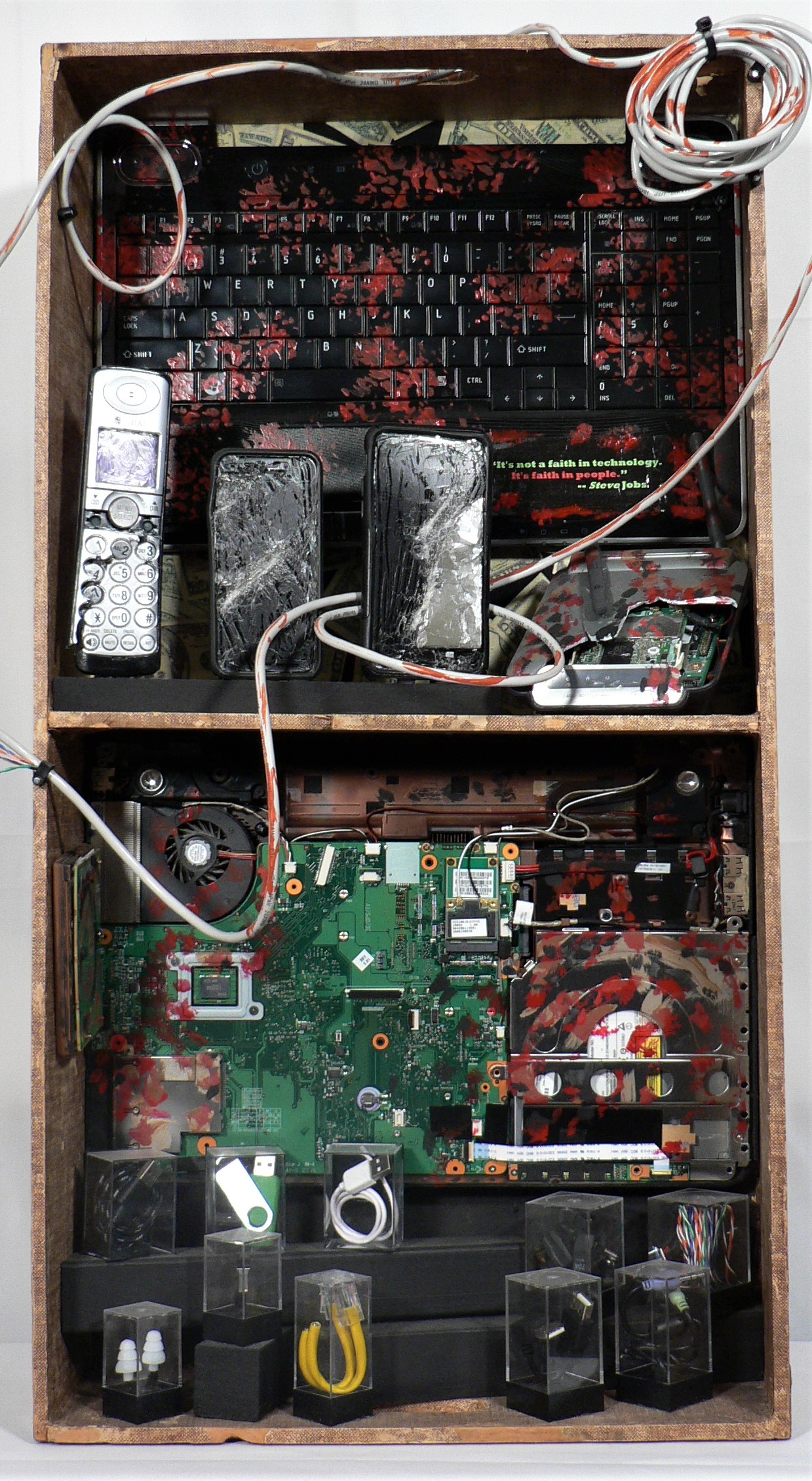 "Breaking Free - ""It's not a faith in technology. It's faith in people."" -- Steve JobsMaterials: Cardboard and wood desk divider; recycled telecommunications and computer gear; acrylic paint; wire; plastic display boxes; paper images; textile; paper. Dimensions: 30""H x 16""W x 5""D. Created: May 2018.Status: For Sale ($400)"