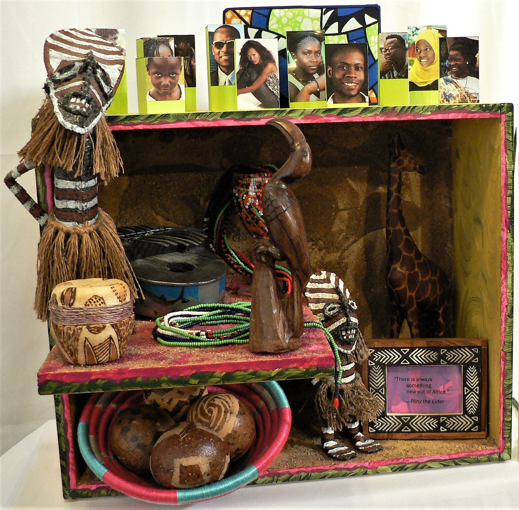 "54 Africas - ""There is always something new out of Africa."" -- Pliny the ElderMaterials: Shagaan Zambezi dolls; African hand-carved wood animals; African 'monkey apple' balls; photo frame; Freedom from Hunger photo (gift to the artist); African necklace beads; African basket; wood dresser drawer; sand; African sardine can musical instrument; drum-shaped votive candle holder; African face images from the internet; barbeque satay sticks; cloth gift box lid; glass goblet; acrylic paint; paper. Dimensions: 17""H x 17""W x 14""D. Created: September 2018.Status: For Sale ($250)"
