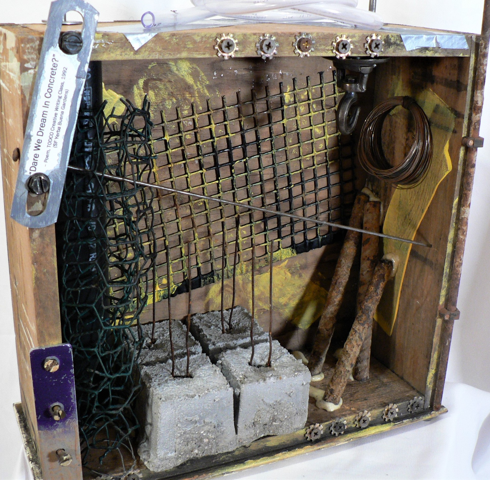 "Constructive Criticism - ""Dare We Dream In Concrete?"" – Poem, TODCO Creative Writing Class, 1992 (SF Yerba Buena Gardens).Materials: Recycled wood drawer; concrete footings; plastic screen; steel wool; metal hardware and screws; plastic tubing; chicken coop wire; metal wire; duct tape; acrylic paint. Dimensions: 19""H x 12""W x 5""D. Created: July 2019.Status: For Sale ($150)"