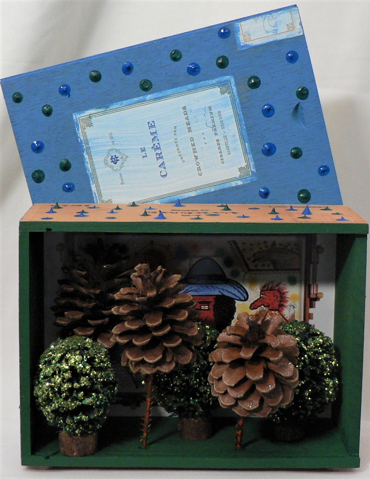 """You Can't See de Forest for da Trees - """"Create art that makes you happy."""" – Roy de ForestMaterials: Cigar wood box; Roy de Forest postcard (Brian Gross Fine Art); model railroad trees; glitter; pine cones; acrylic paint. Dimensions: 10""""H x 7""""W x 3""""D. Created: August 2019.Status: For Sale ($75)"""