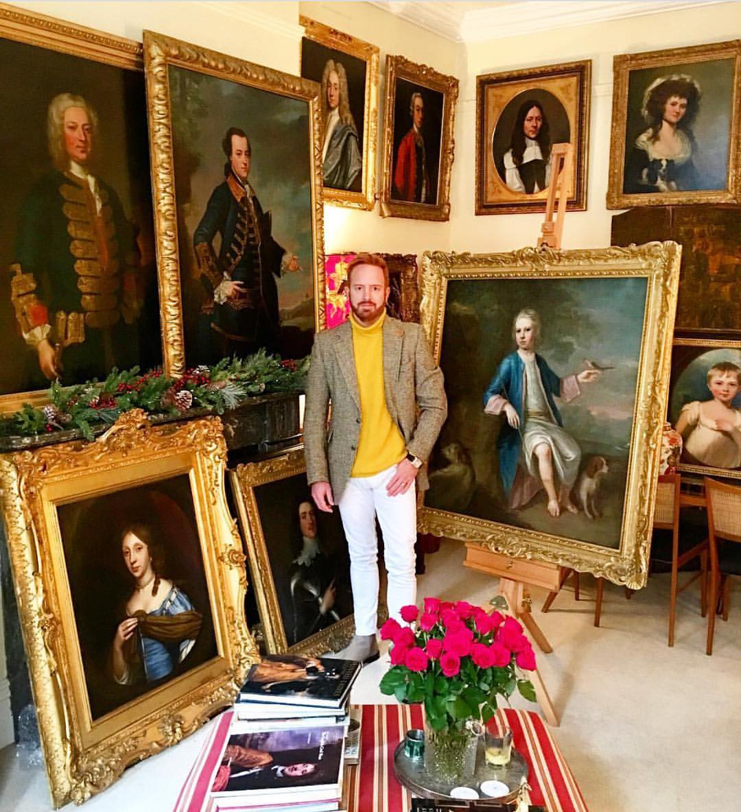 Nick Cox with his ornately framed portraits in his apartment