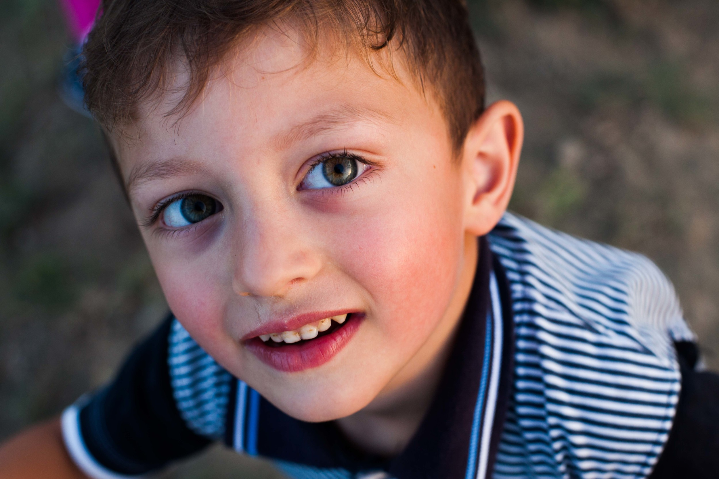Hamltik, a young boy, stops for a portrait in between playing with his sister and his neighbor.