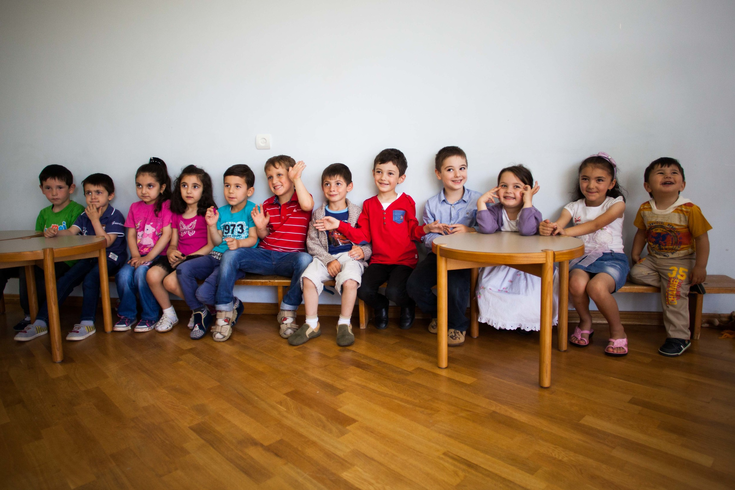 Children at the local YMCA in Spitak sit in a row eager to meet the American students who have come to visit.