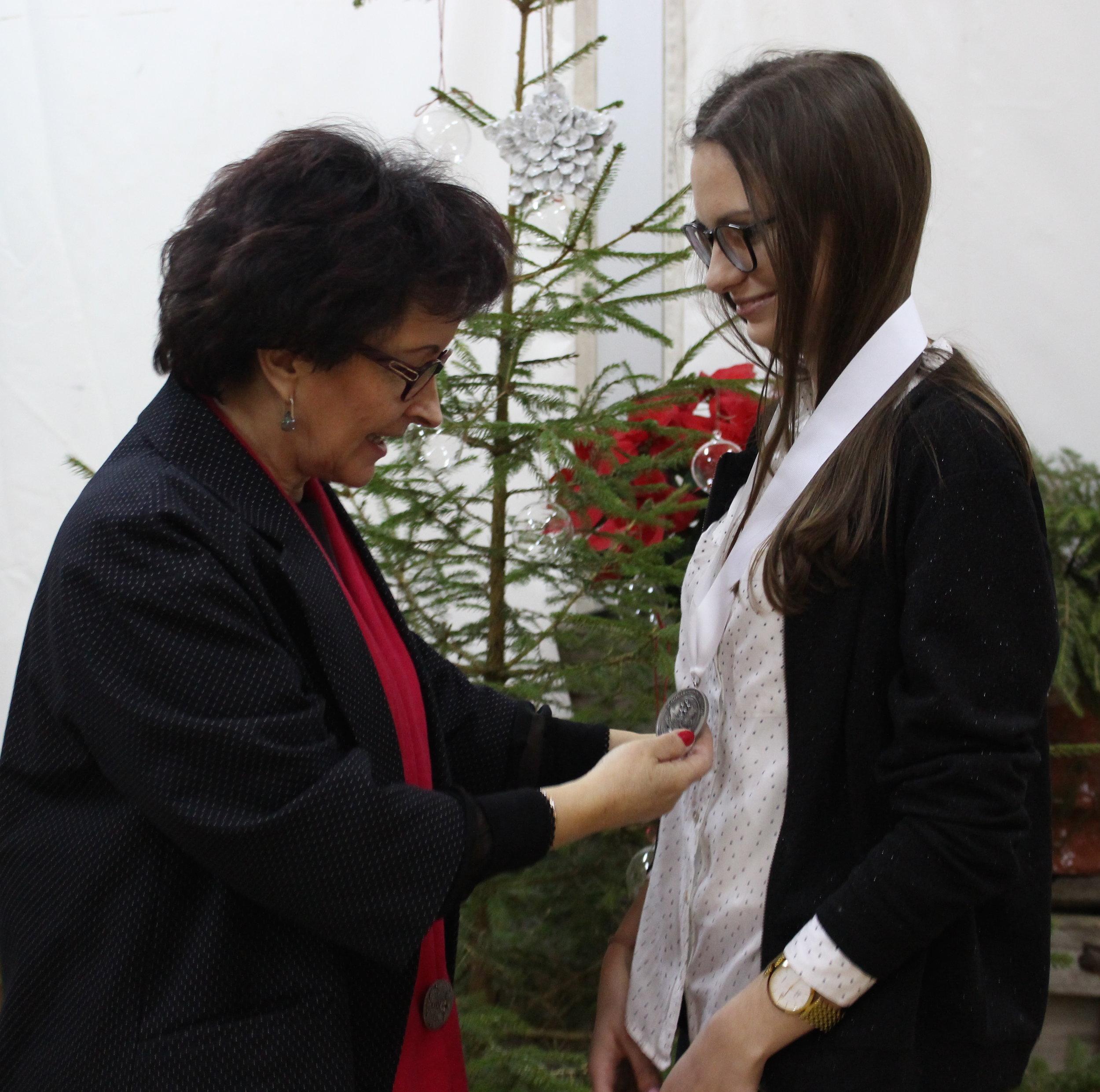 Dominika Wozniak receiving the International Scholarship of Honor  medal in Poland from Barbara Margol  of the Nidzica Foundation