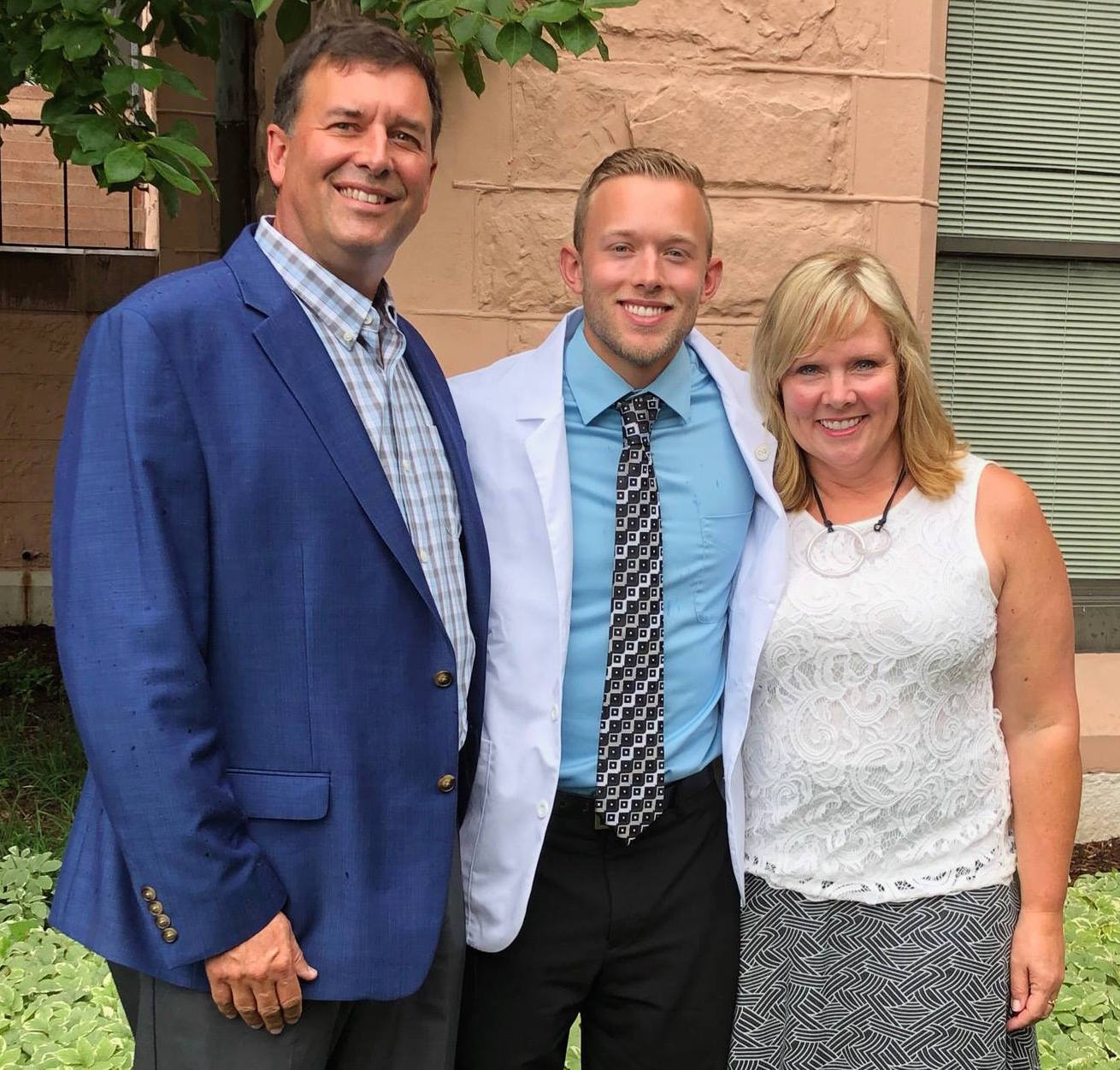 Luke with his parents at his white coat ceremy