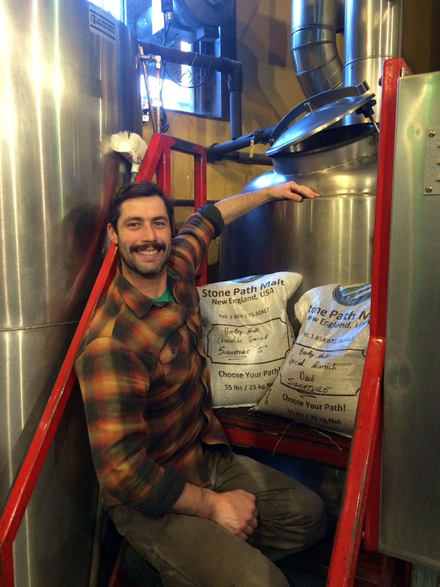 Matt Gallagher, Head Brewer, Portsmouth Brewery poses with our specialty malt and a kettle of Downtown Brown!