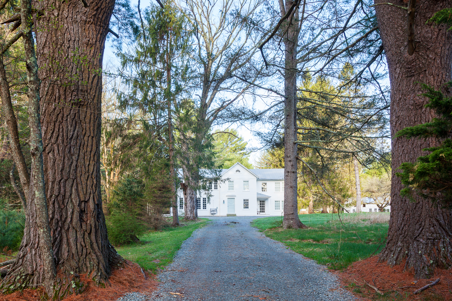A long driveway leads to the historic Floating Farmhouse, a Catskills vacation rental and wedding venue in upstate New York.