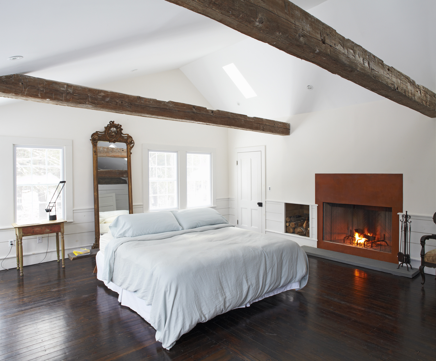 Master bedroom fireplace and antique ceiling beams in the Floating Farmhouse Catskills vacation rental in upstate New York.