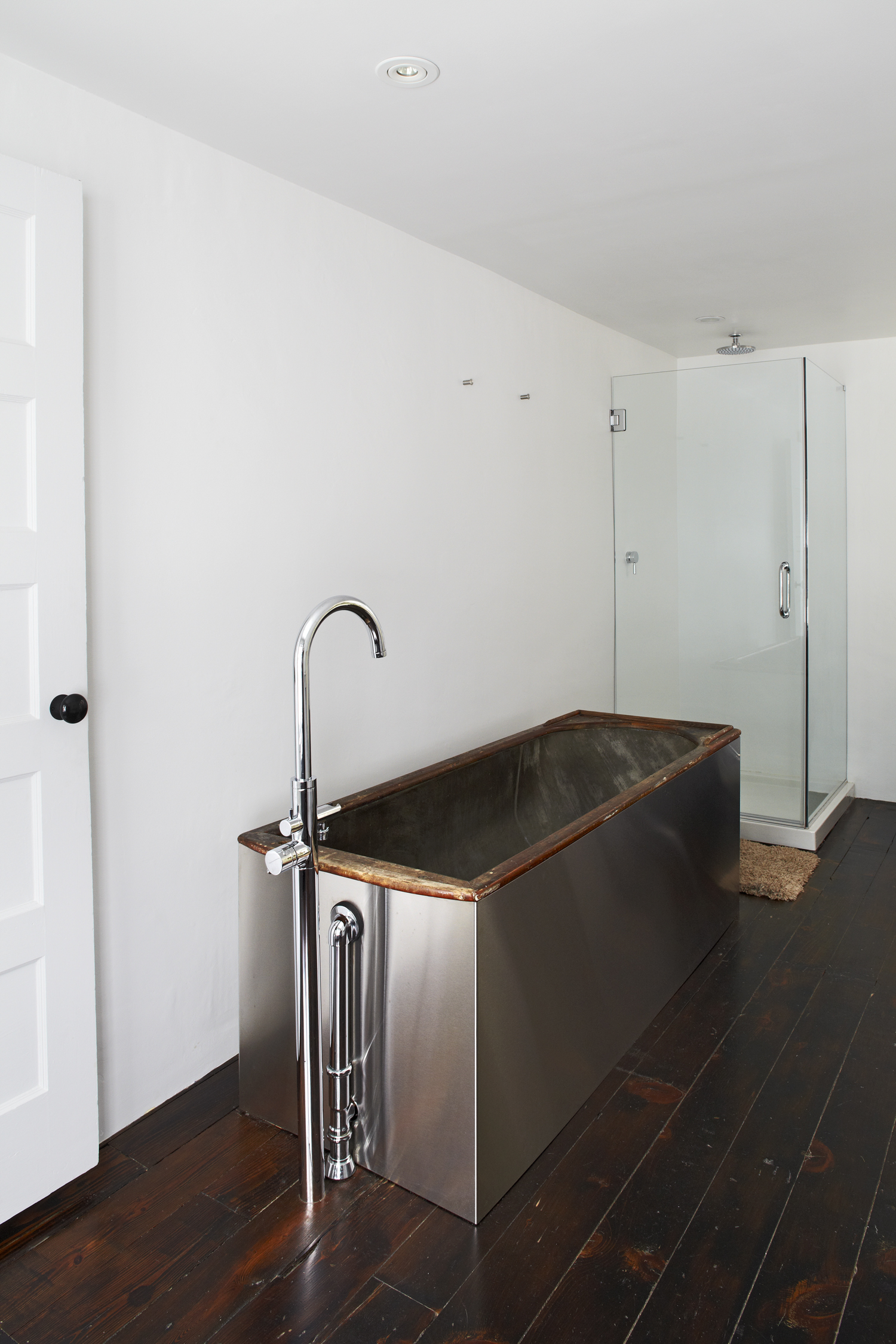 Antique wood and copper bathtub, wrapped in stainless steel, in the Floating Farmhouse Catskills vacation rental in upstate New York.