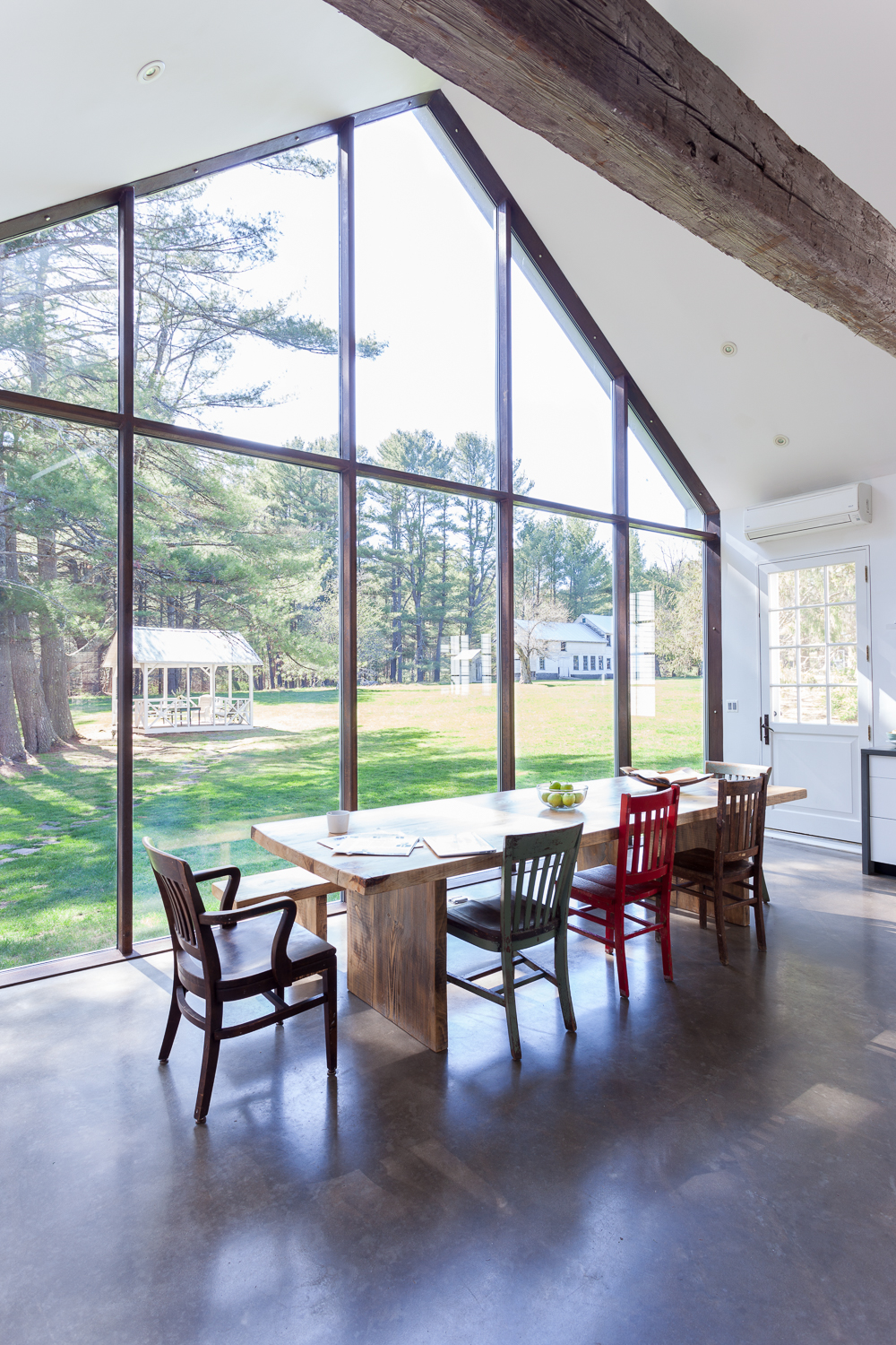 Kitchen glass wall overlooking water, apple trees and barn in the Floating Farmhouse Catskills vacation rental in upstate NY.