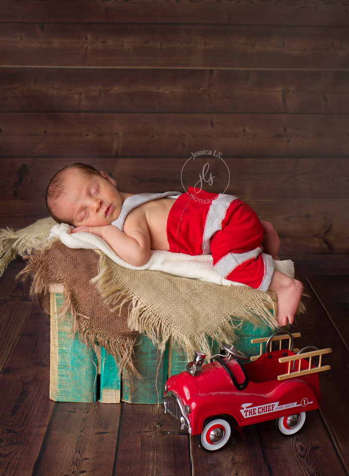 Newborn baby with firetruck on wooden box in Woodbridge VA studio with Jessica LS Photography