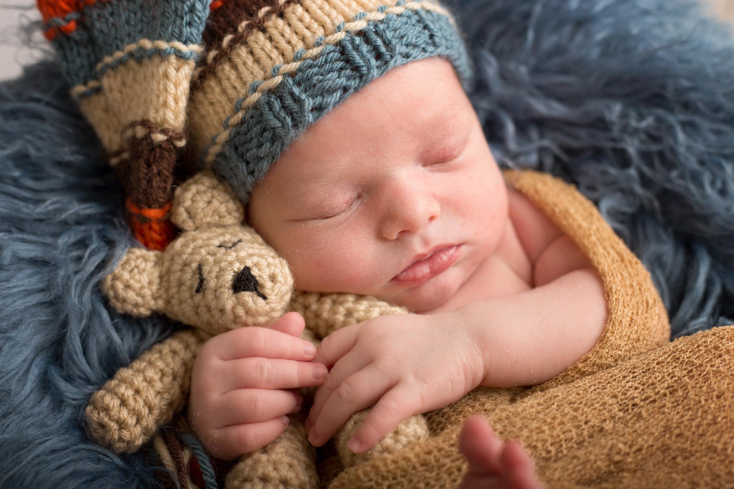 Newborn baby boy with sleeping teddy bear in Woodbridge VA studio