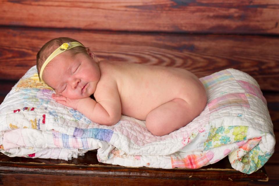 newborn baby girl on quilt