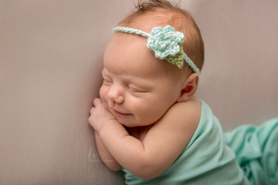 baby girl in mint and beige smiling in studio