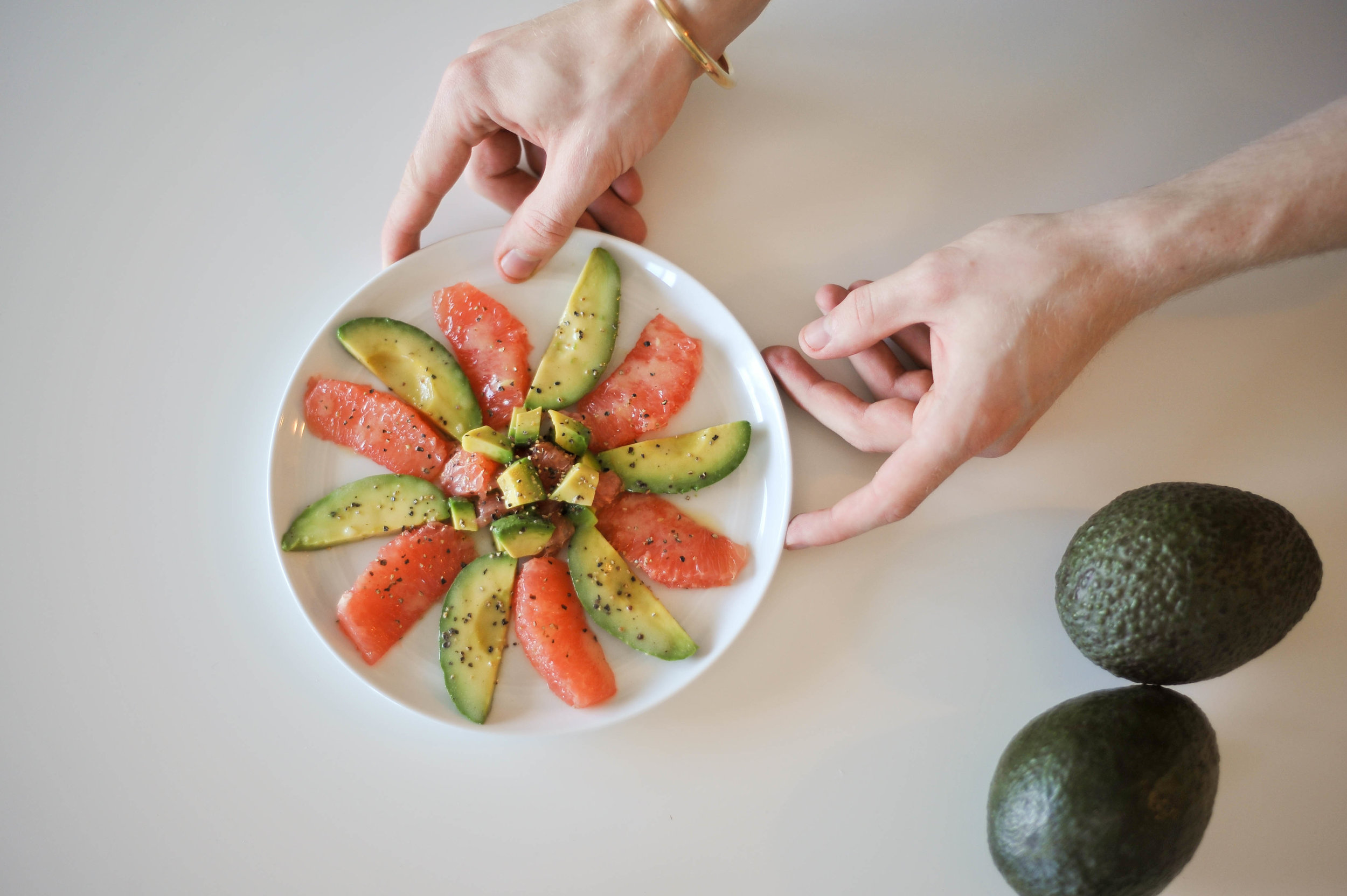 Slices of avocado and grapefruit on a plate.