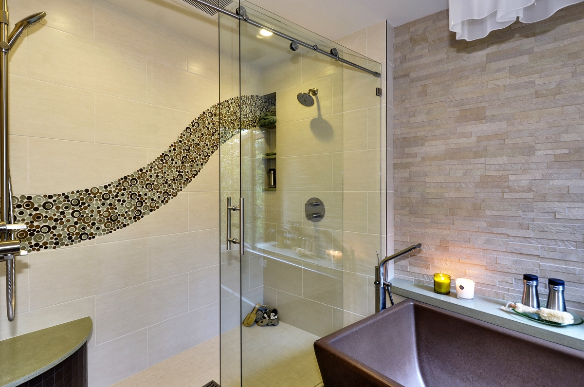 Glass bubble tile - water jet cut tiles inlaid in porcelain tile to create wave pattern. Barn door style glass shower door.