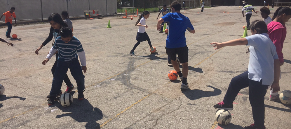NCNAA students work with coaches from Scott Gallagher Soccer on the existing play surface.