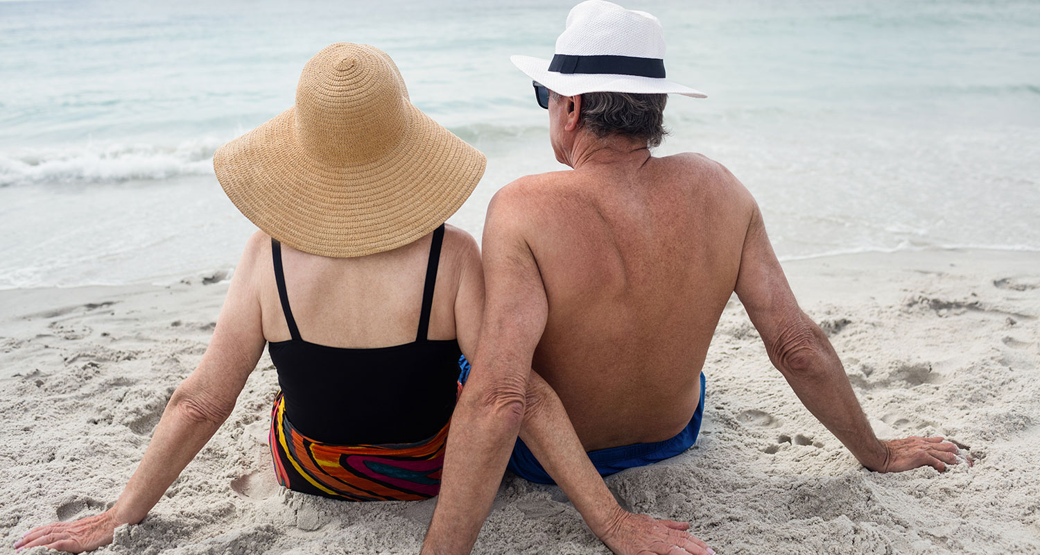 older couple laying on beach photo