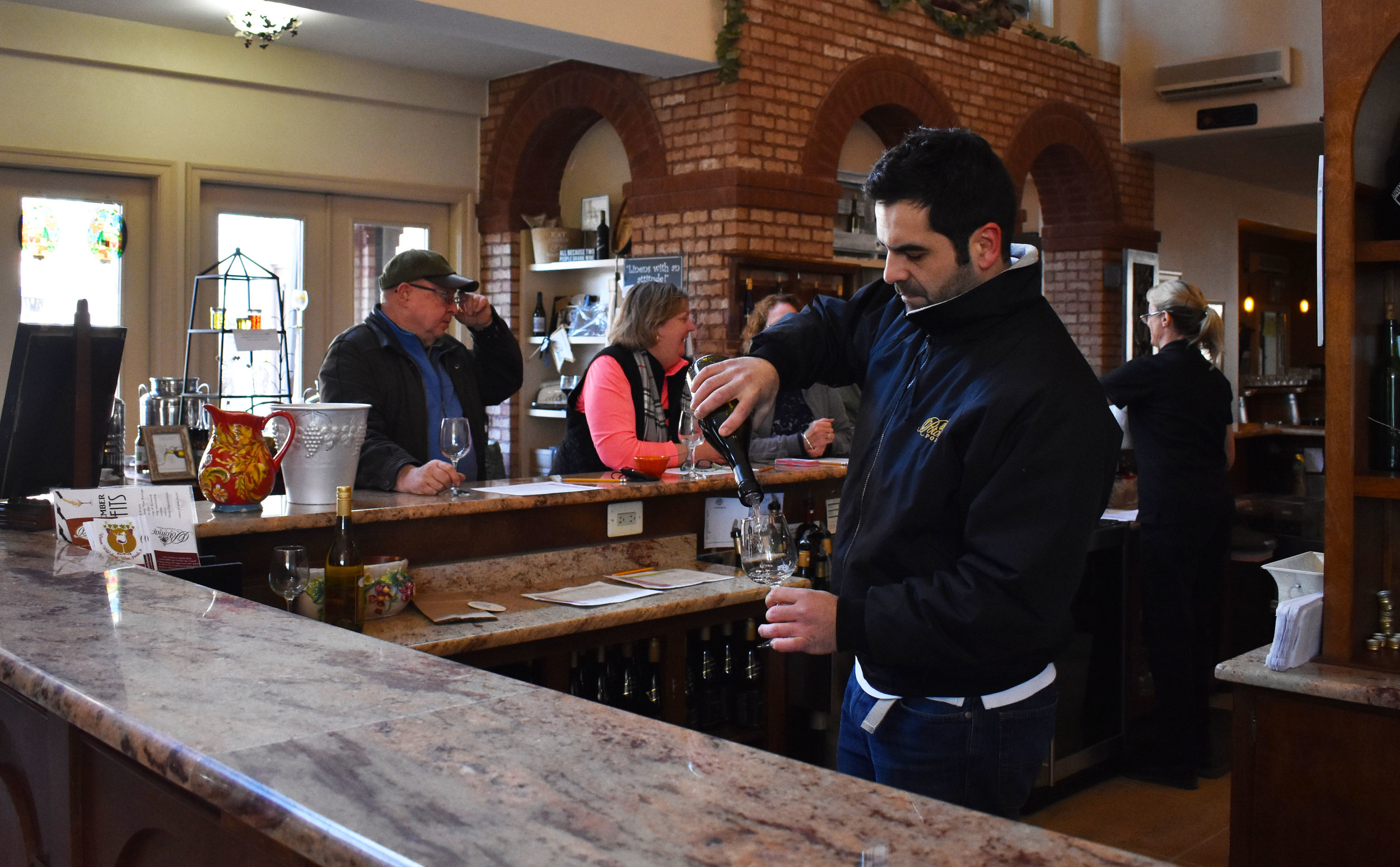 Head winemaker   David Pagan Castaño pours a bottle of white wine in the tasting room at Potomac Point Vineyard and Winery in Stafford, Va., Friday, Feb. 2, 2018. (Lindsey Leake/American University)