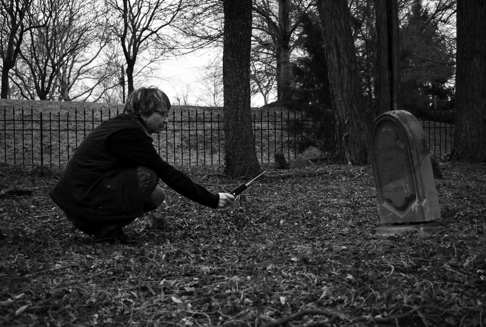 Paranormal investigator Lori Miars, co-founder of Northern Virginia Spirits and Paranormal Investigators, reaches out to the dead at Broad Run Cemetery in Ashburn, Va., Tuesday, Feb. 13, 2018. According to a plaque beside the graveyard, 35 family members and friends of John LeFevre, whose family once owned and farmed the land, were buried there between 1750 and 1911. (Lindsey Leake/American University)