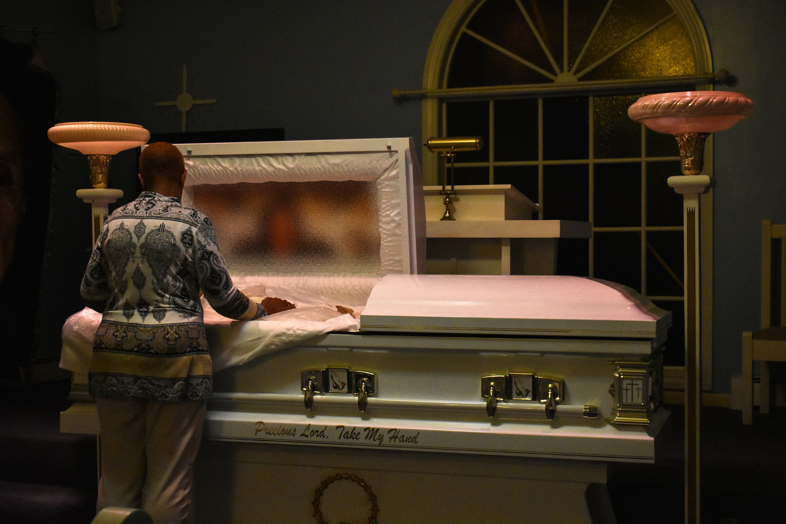 Funeral director Donita Greene views a decedent ahead of a visitation at Greene Funeral Home in Alexandria, Va., Thursday, Oct. 18, 2018. This image has been partially blurred to protect the identity of the deceased. (Lindsey Leake/American University)